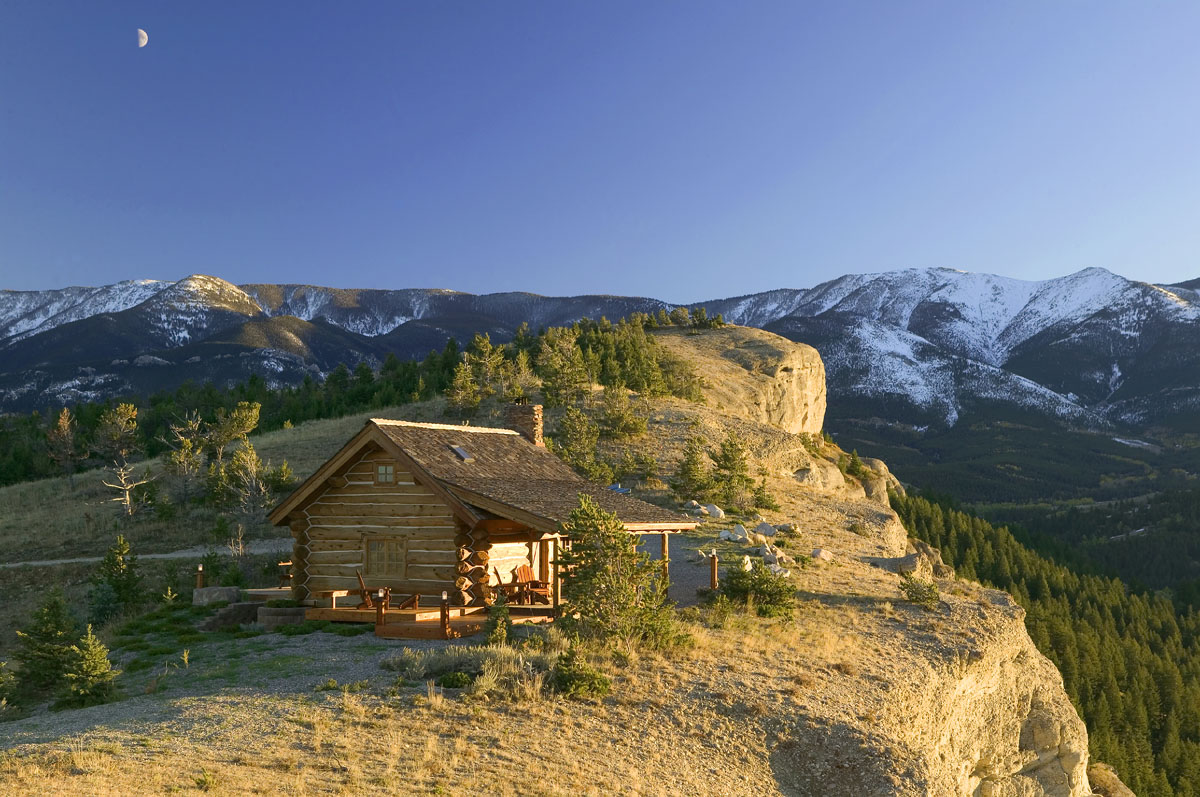 Small log cabin perched cliffside in montana cabin living