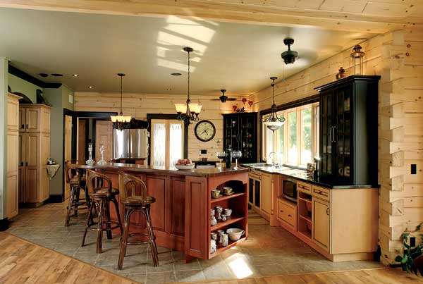 The kitchen's cherry island with wood top is the perfect gathering place for family and guests. Stained upper cabinets and granite counters contrast with the natural wood tones of the walls and flooring. Glass doors lead to the home's sunroom.