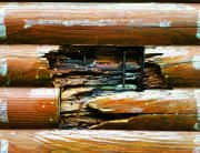 Neglect rarely leads to rot, but when it does, repairs proceed quickly because all the wood is exposed. Here the rot is dug out and any metal fasteners are removed. The remaining wood is smoothed with wood epoxy and the new log pieces are positioned.
