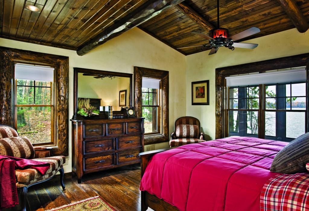 Lakeside bedroom wood beams red bedspread