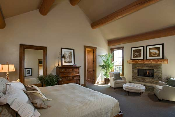 The Large Master Bedroom Includes Exposed Log Rafters And Has A Comfortable Seating Area Next To