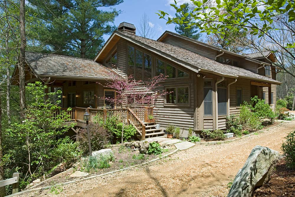 A gradually sloping small-pebble driveway leads to the front of this Blue Ridge Mountains home. The exterior of the home is painted dark brown to match the tree trunks in the surrounding forests.