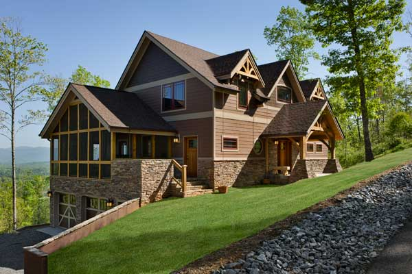Riverbend Timber Framing modified a larger plan by decreasing the square footage to fit the client's needs. Builder Bill Berg notes that placing the garage under the screened-in porch is a great space saver. The foundation is a dry-stacked stone veneer; the siding is a wide horizontal fiber-cement board. Windows and doors enhance the Craftsman look.