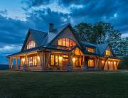 The canted timber frames of the 360-degree porch let visitors know something different is going on in this Vermont hilltop timber frame.