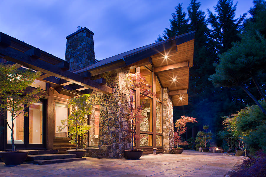 The juxtaposition of stone, wood and metal create a distinctive look for the 2,350-square-foot home, and help it to harmonize with its rugged surroundings. A natural landscape design approach enhances the look.