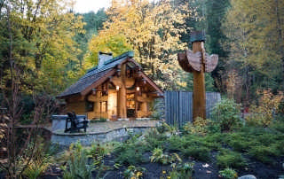 "This 450-square-foot log guesthouse is surrounded by a man-made pond on 10 acres near the Cheakamus River in British Columbia, Canada. The property also houses two other log homes. Since the home-owners are hot tub devotees, the spa in the foreground is an important part of the design. At night, the home known as ""The Totems"" is aglow in the wooded setting."