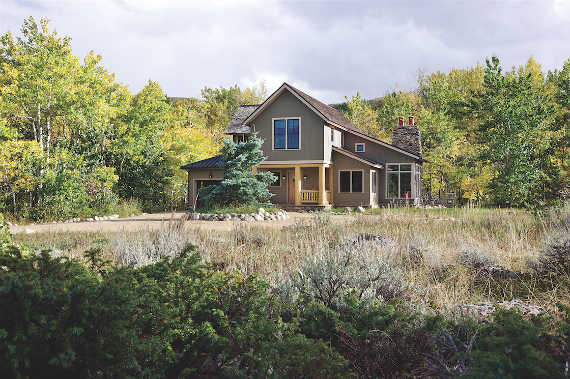 Set in Red Lodge, Montana, this custom home was designed by architect Andrew Porth as a vacation cabin for his family and friends. The two-story core is finished with vertical tonque-and-groove cedar boards painted a greenish gray. The single-story sections feature cedar shingles in a taupe tone. The small square windows admit light to the upper part of the curved vaulted ceilings in the living room.